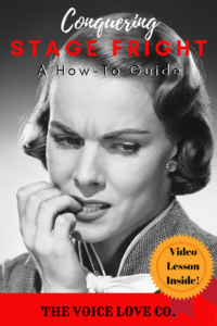 An actress bites her nails while casting her gaze to the floor. She is obviously filled with anxiety. Conquering Stage Fright: A how-to guide. Free video inside. From The Voice Love Co. voicelove.co