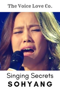 Sohyang sings into a microphone. The Voice Love Co. presents Singing Secrets of Sohyang.