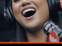 """Morissette Amon sings into a microphone with a smile. Text reads: Voice Coach Reacts. Morissette singing """"SHINE"""" here at The Voice Love Co."""